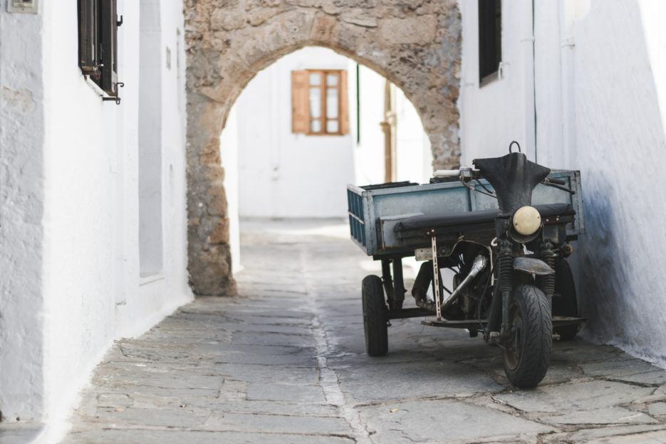 A moped in one of the narrow streets of the Greek town of Lindos, Rhodes - from travel blog: https://epepa.eu/