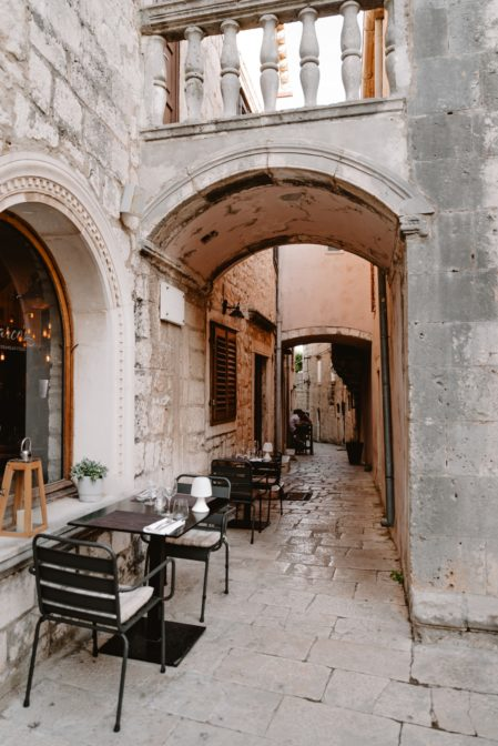 Restaurant tables in a narrow street of Korčula Old Town, Croatia